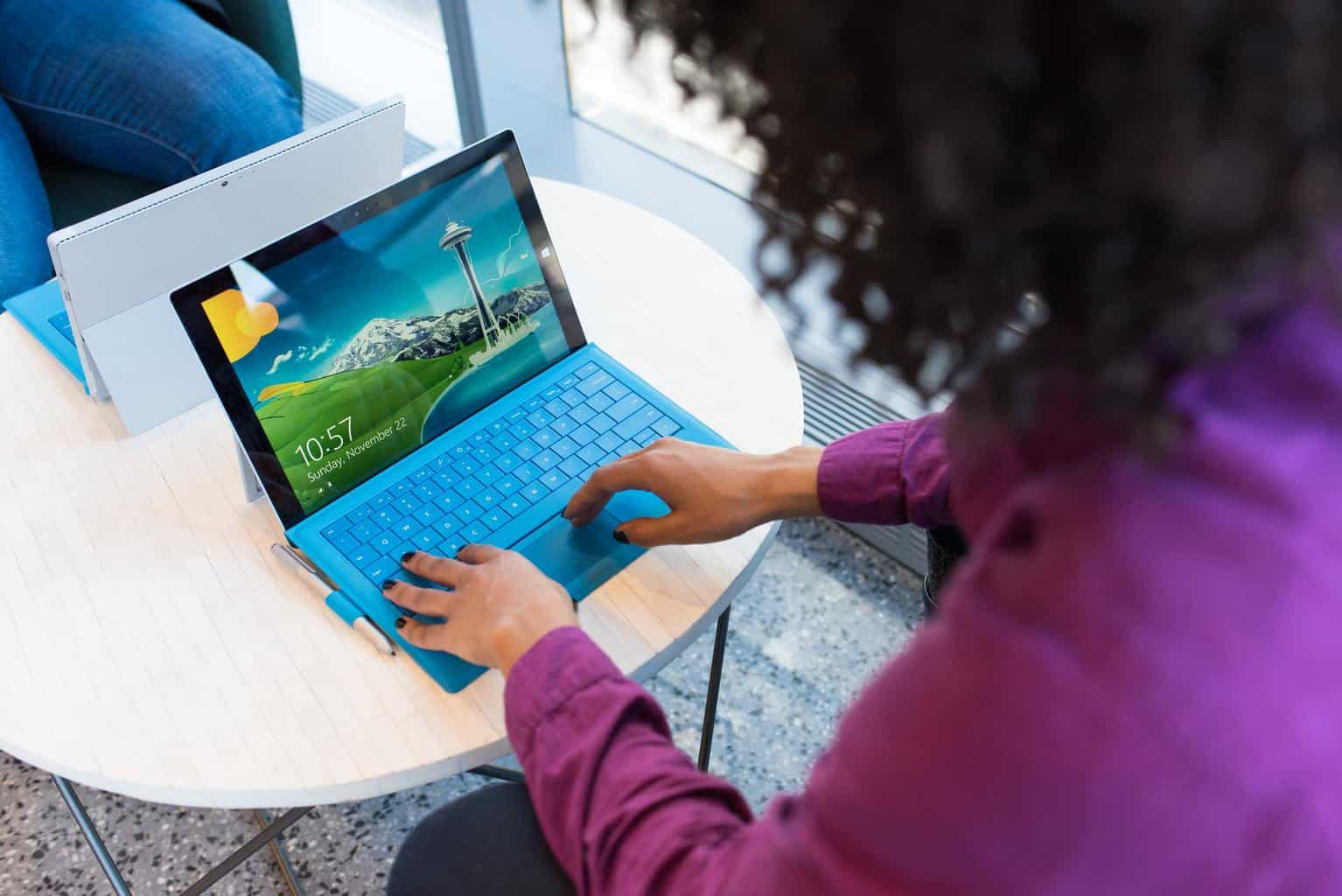 Woman typing on blue laptop